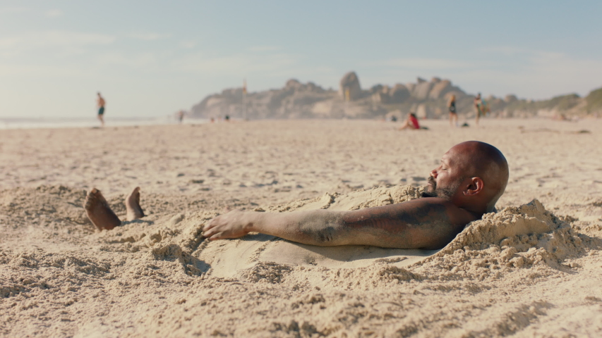 funny man covered in sand on beach enjoying summertime having fun relaxing on warm sunny day 4k