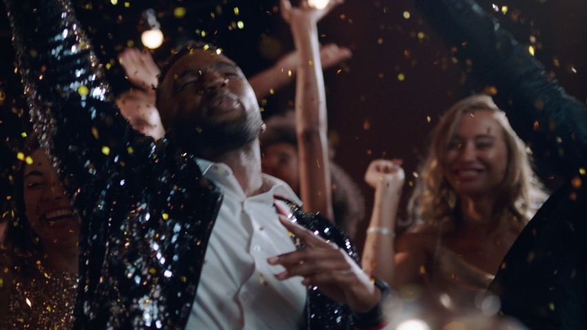 Friends celebrating new years eve party dancing throwing confetti enjoying glamorous celebration countdown wearing stylish fashion at formal social gathering on rooftop at night 4k | Shutterstock HD Video #1034056799