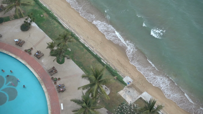 Aerial top down view of beach side resort swimming pool, fun family day in the tropics #1034057756
