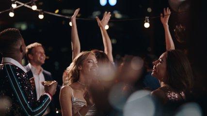 happy group of friends celebrating new years eve party dancing throwing confetti enjoying glamorous celebration wearing stylish fashion social gathering on rooftop at night 4k