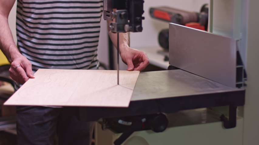 Guitar maker cutting wood guitar backboard   Shutterstock HD Video #1034058455