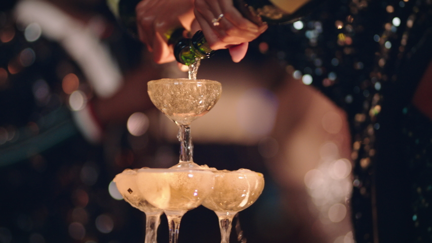 Happy celebration woman pouring champagne tower at glamorous dance party celebrating with friends enjoying crazy nightlife wearing stylish fashion dancing on rooftop at night 4k footage