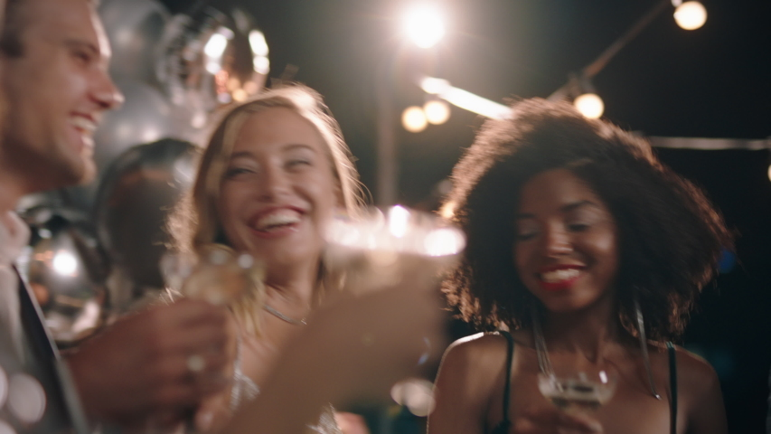 Group of stylish friends celebrating at glamorous rooftop party event making toast drinking champagne at formal social gathering enjoying evening celebration at night 4k