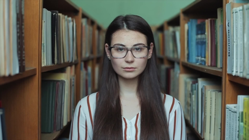 Bobruisk, Belarus - 11 April 2019: Portrait of young beautiful girl in library. Female student studying among lot of books between shelfs.