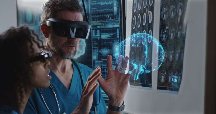 Medium close-up of a male and a female doctor examining 3D brain hologram while wearing VR headsets | Shutterstock HD Video #1034083976