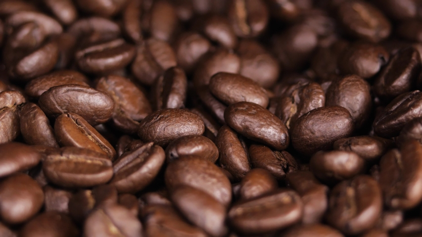 Roasted coffee bean. Fragrant coffee beans scrolls slowly around the camera. Slow Motion Close Up of Whole Roasted Coffee Beans. | Shutterstock HD Video #1034084159
