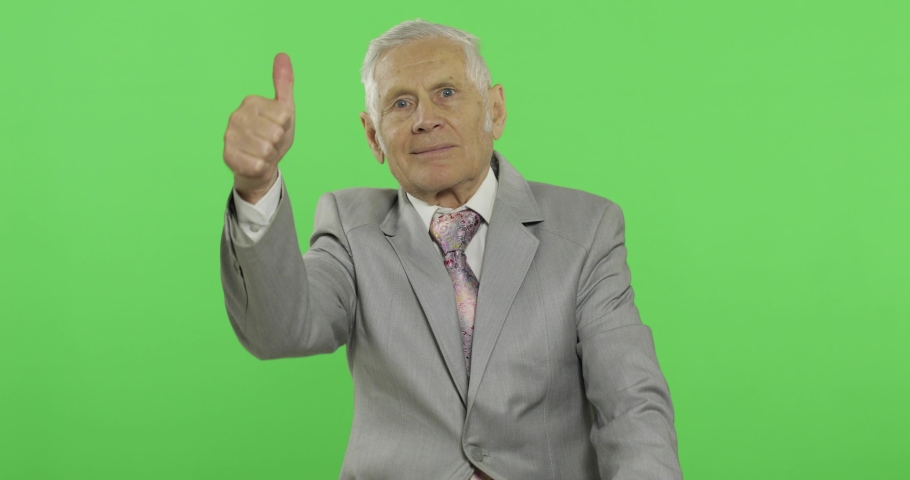 Elderly businessman giving thumb up. Old man in formal wear showing thumb up gesture on chroma key background. Symbol of agreement and success. Green screen background