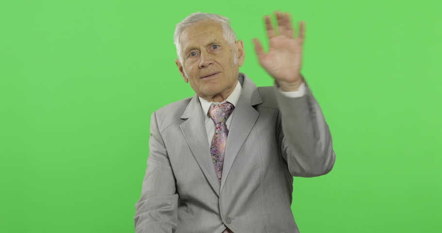 Elderly businessman waving with hands to camera. Old man in formal wear on chroma key background. Place for your logo or text. Green screen background   Shutterstock HD Video #1034085668