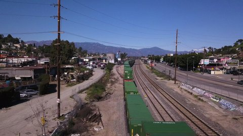 Los Angeles, California / United States - 03 29 2019: Freight train driving through Hollywood, LA streets, aerial tracking view
