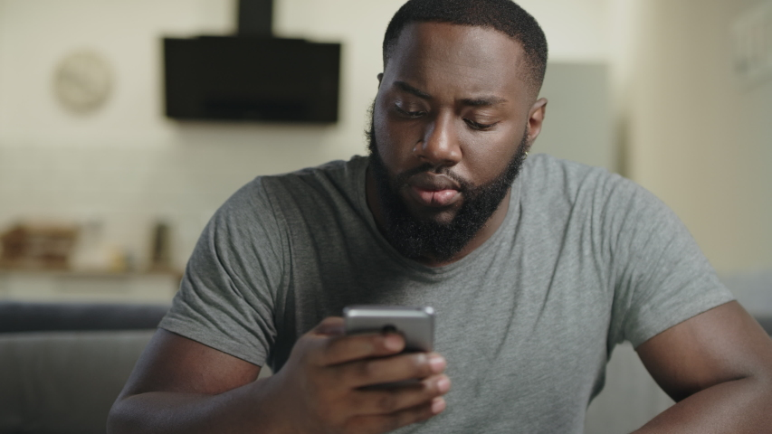 Black man holding phone in hand at open kitchen. Focused guy texting in smartphone. Surprised person looking at mobile phone at kitchen. Black male person getting news by cellphone. Royalty-Free Stock Footage #1034089193