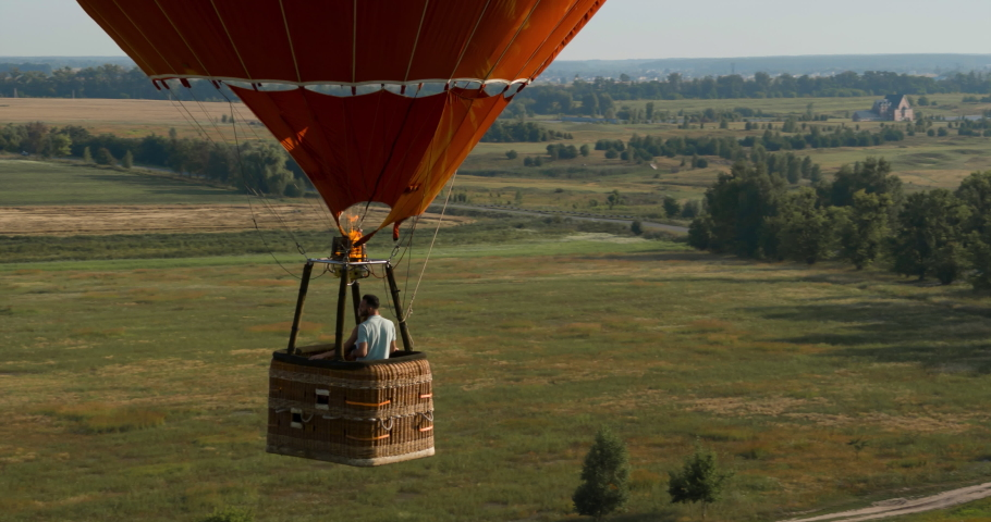 Flying near Air Balloon with Hugging Couple in Basket Aerial 4K Video