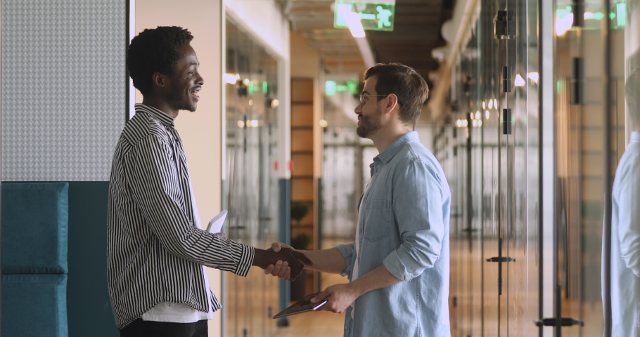 Diverse male partners talking handshaking standing in office hallway, satisfied african american business man shaking hand of caucasian colleague thanking for help advice meeting in company corridor #1034098895