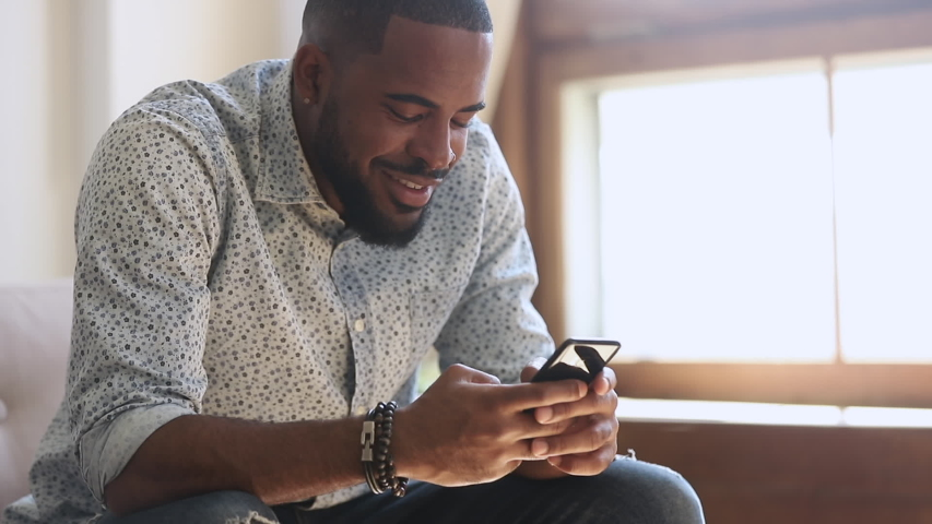 Young african american man holding smartphone device texting sms message sitting at home office, smiling black guy using apps playing mobile game chatting in social media surfing web on phone indoors