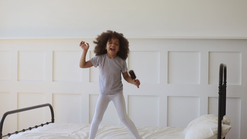 Funny adorable happy kid girl jump on bed sing in hairbrush microphone, cute little african american child having fun dancing to music playing in bedroom alone enjoy pretending singer in the morning Royalty-Free Stock Footage #1034099159