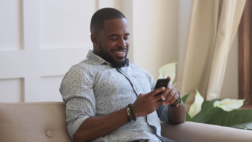 Smiling young black man holding phone using mobile apps for work education shopping online sit on sofa, happy african american guy texting sms message in social media play game on smartphone at home Royalty-Free Stock Footage #1034099162