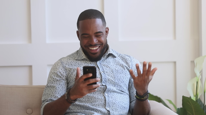 Surprised excited black man winner hold smartphone read good internet news amazed by mobile online bet bid game win, happy african guy look at cell phone screen overjoyed by victory success at home Royalty-Free Stock Footage #1034099171
