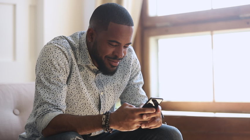 Smiling african american man holding smartphone texting sms message or play mobile game sit on sofa at home, happy young black guy using social media app work study on cell phone looking at screen Royalty-Free Stock Footage #1034099195