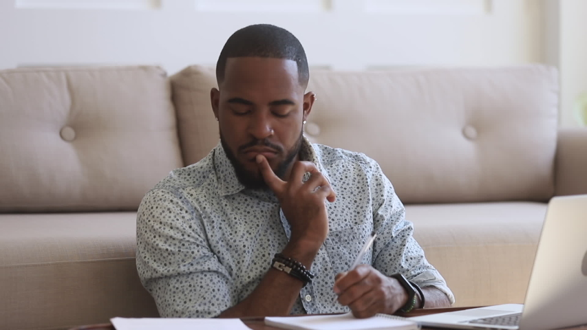 Focused african american man student freelancer study typing on laptop doing paperwork, serious young black man working distantly from home pay bills online prepare for test exam sit on floor at home Royalty-Free Stock Footage #1034099204