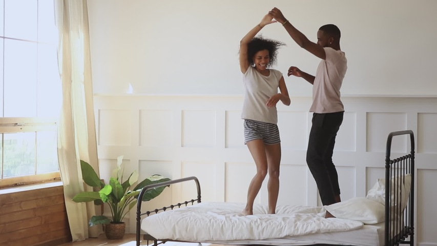 Happy young romantic african couple holding hands dancing laughing standing on bed, carefree active black husband and wife wear pajamas having fun bonding enjoy morning dance in bedroom interior #1034099210