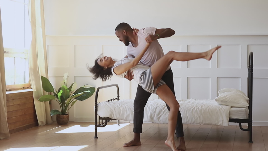 Happy active romantic black husband and wife enjoy slow dance spinning in bedroom interior, cheerful african couple wear pajamas dancing together having fun in morning activity laugh bonding at home | Shutterstock HD Video #1034099222
