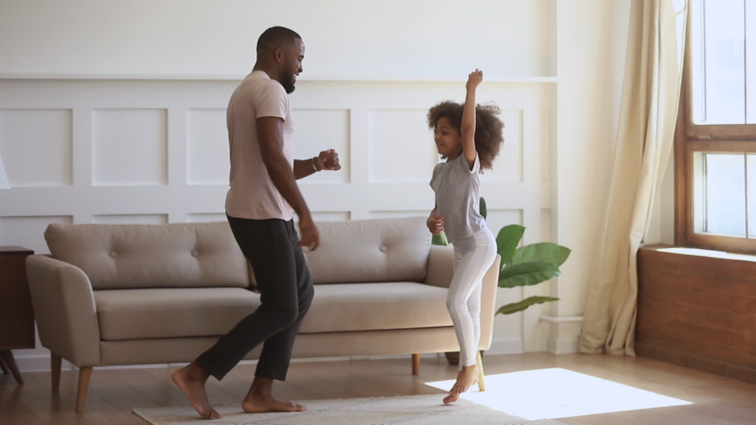 Happy funny carefree african family father and cute little kid daughter jumping having fun together in living room, dad dancing with small child girl enjoy music active morning playing at home