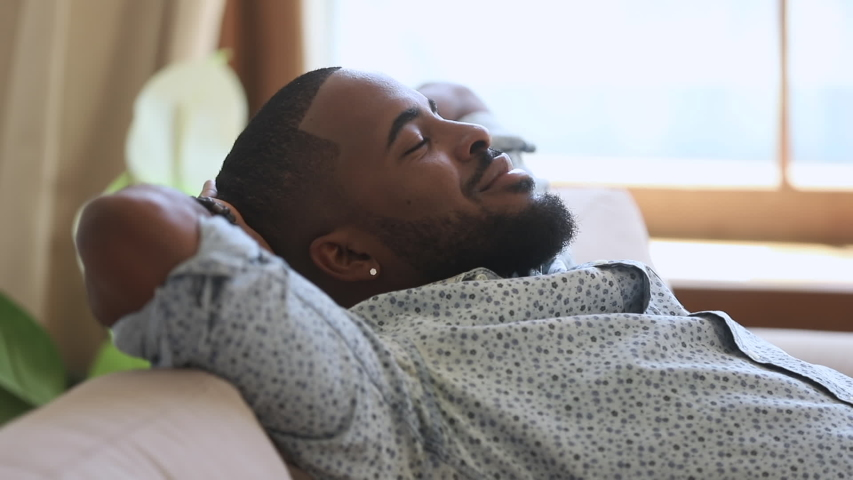 Calm relaxed african american young man resting napping on sofa with eyes closed at home, happy healthy guy breathing fresh air lounge on couch hands behind head enjoy stress free peaceful day | Shutterstock HD Video #1034099249