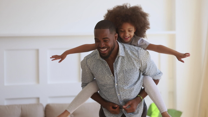 Happy family loving black dad giving cute little funny kid daughter piggyback ride spinning at home, cheerful african father carrying small child girl on back bonding having fun playing together #1034099258