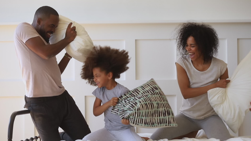 Cute funny small african american kid daughter playing pillow fight on bed with happy parents, carefree black family having fun with little child girl laughing enjoy morning activity game in bedroom | Shutterstock HD Video #1034099267