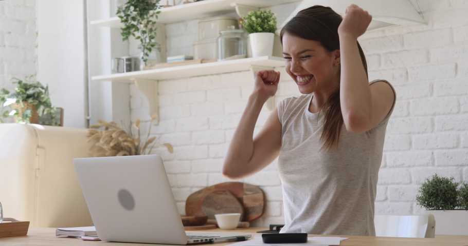 Overjoyed girl student celebrate online win success read great news using laptop feel amazed sit at home, happy excited woman looking at computer surprised got good test exam result scholarship