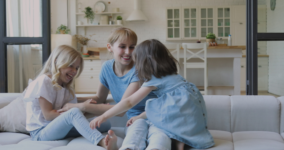 Happy family young mom baby sitter tickling small funny kids daughters laughing playing together on sofa, mother having fun with little cute children siblings at home relaxing cuddling on couch