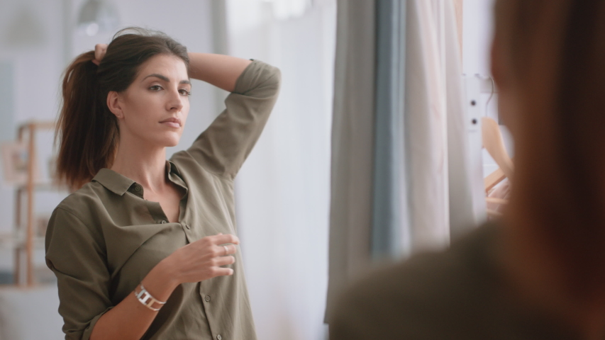 Beautiful young woman getting dressed looking in mirror fresh start to new day putting on clothes enjoying morning at home positive self image 4k footage | Shutterstock HD Video #1034109608