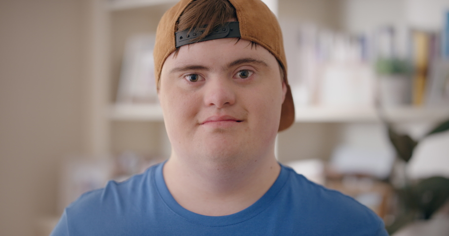 smiling boy with down syndrome happy special needs teenager with disability at home testimonial concept 4k Royalty-Free Stock Footage #1034111177