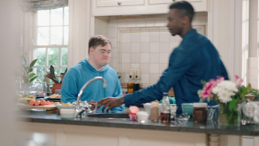 Multi ethnic father and son dancing in kitchen teenage boy with down syndrome having fun dance with dad celebrating happy family at home