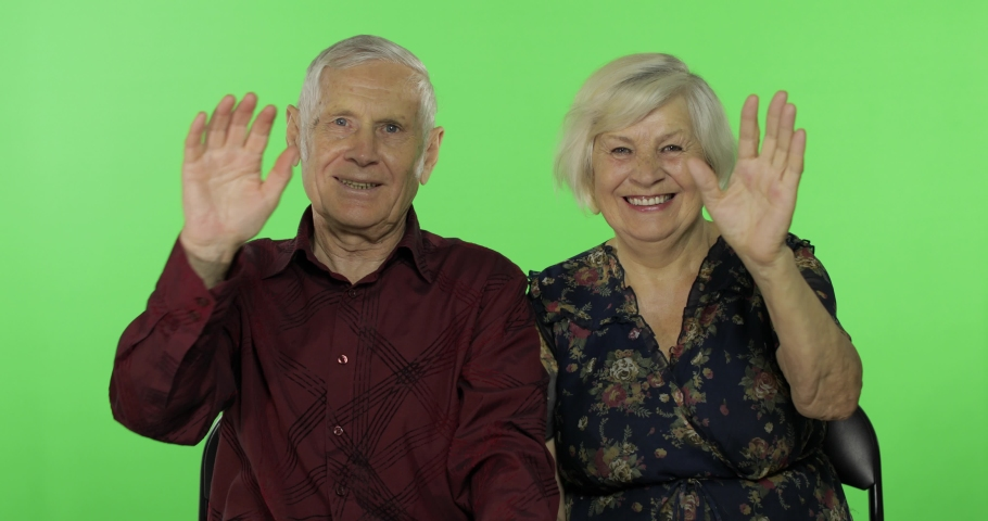 Senior aged man and woman waving with hands to camera on chroma key background. Concept of a happy family in old age. Place for your logo or text. Green screen background