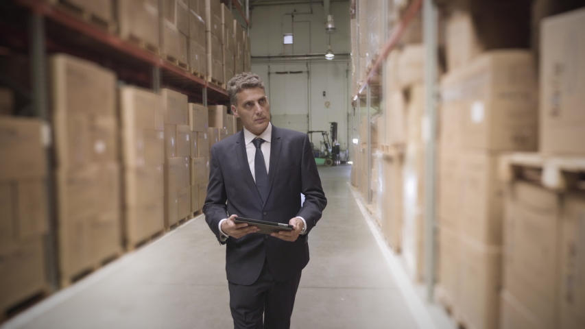 Medium shot of businessman with digital tablet while maintaining records in warehouse #1034131259