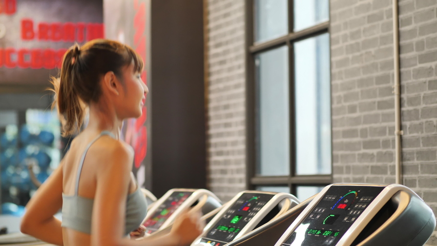 Young woman running on a treadmill at gym and checks Heart Rate Monitor, Smart Watch. Fitness and healthy lifestyle concept.  Slow motion | Shutterstock HD Video #1034135717
