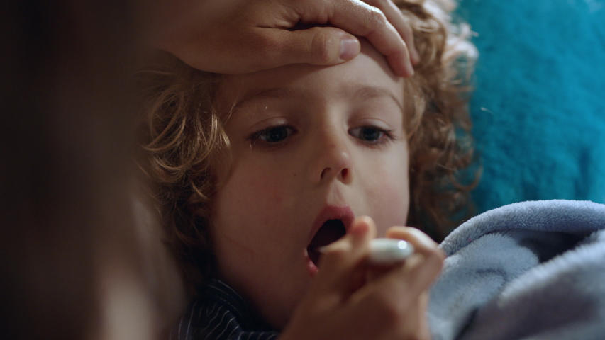Mother caring for sick child lying in bed with flu measuring temperature using thermometer little boy at home with fever mom giving health care | Shutterstock HD Video #1034147390