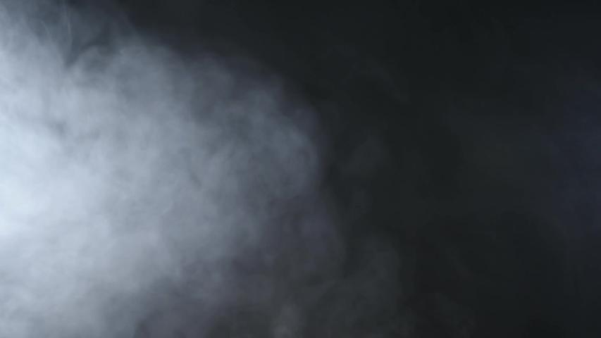 Atmospheric smoke Fog effect. VFX Element. Haze background. Abstract smoke cloud. Smoke in slow motion on black background. White smoke slowly floating through space against black background. #1034159819