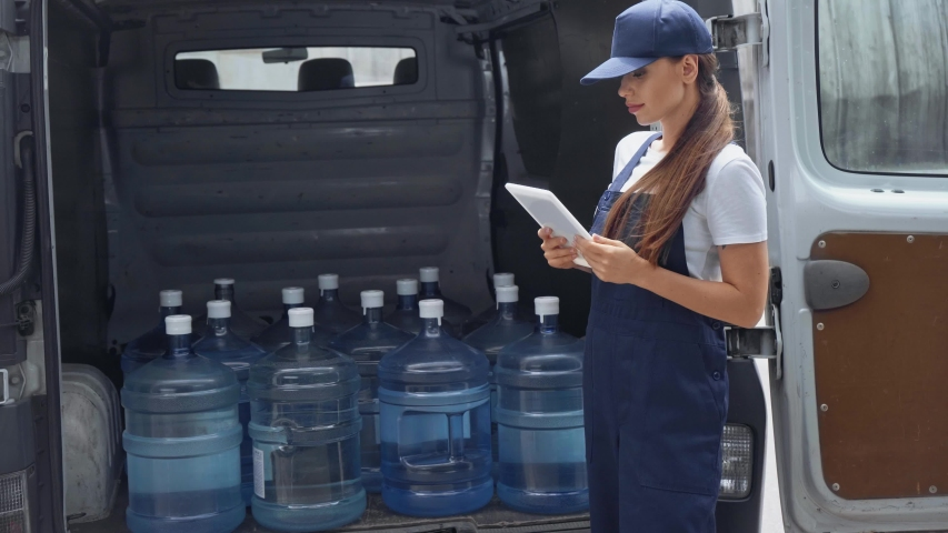 Attractive girl in cap and uniform using digital tablet and touching bottles with water in car