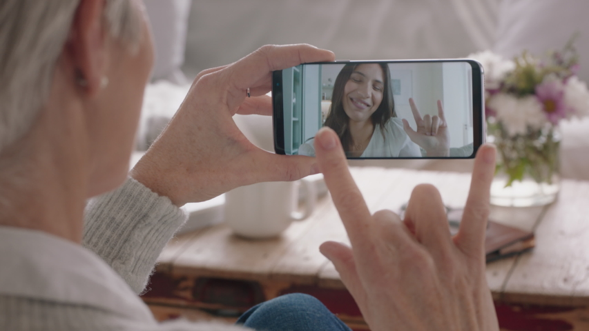 Mature woman having video chat using smartphone deaf mother chatting to daughter with sign language enjoying conversation with family on mobile phone hearing impaired communication | Shutterstock HD Video #1034162471