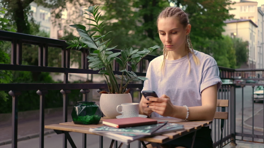 Stylish caucasian woman with pigtails haircut sitting on terrace use smartphone social internet media technology outside loft 5g summer | Shutterstock HD Video #1034171609