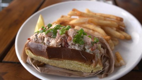 Close up of lemon being squeezed over a lobster roll