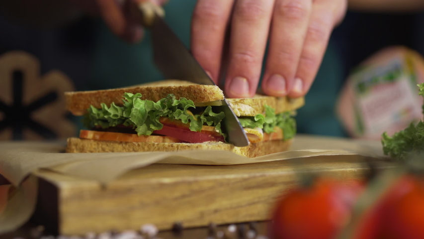 Man cuts club sandwich in a half by sharp knife on a wooden board at the kitchen, making of the fastfood at home, chef is cooking sandwich, Full HD Prores HQ 422 | Shutterstock HD Video #1034175710