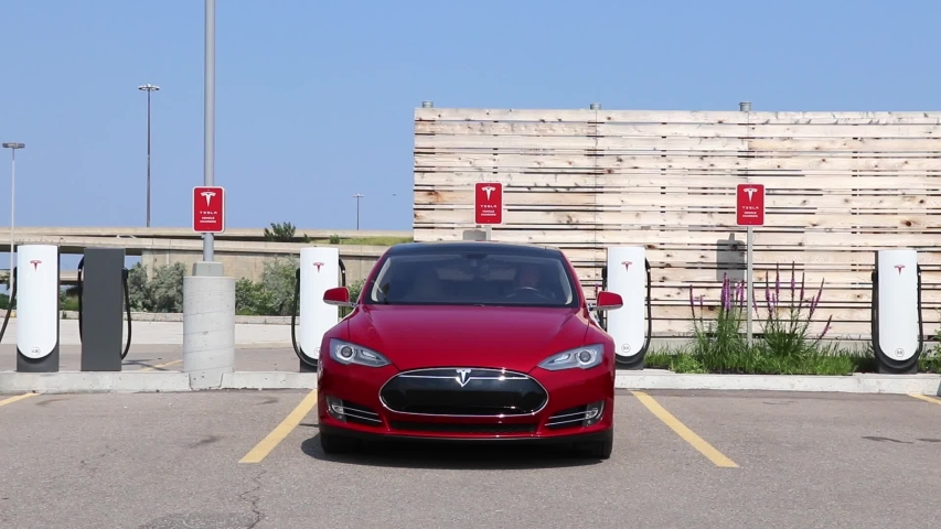 TORONTO, CANADA - July 26, 2019: Red Tesla Model S drives away from Tesla Supercharger location in Toronto (Etobicoke).