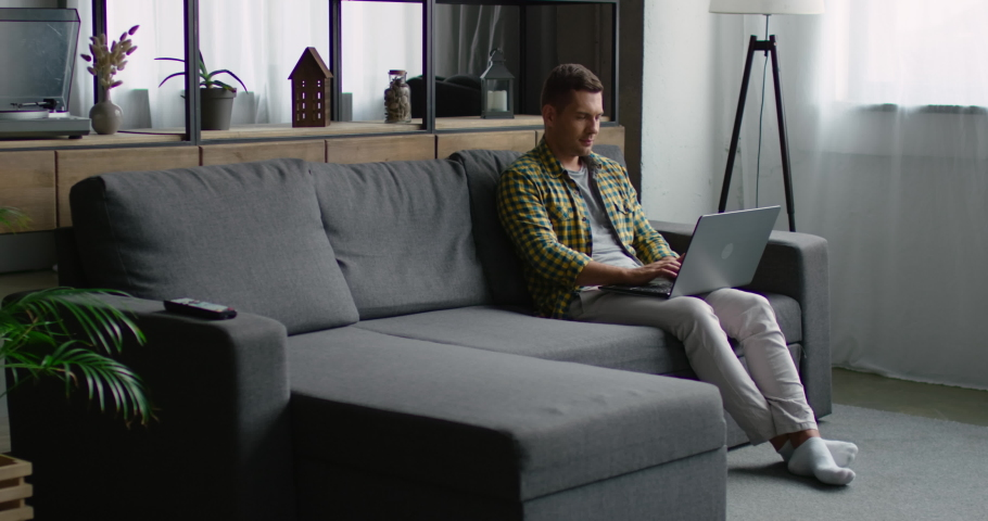 Pretty young girl is approaching and sits down near her boyfriend that is working on his laptop, sitting on a grey couch at home. Slow motion, 4K, shot on RED camera. | Shutterstock HD Video #1034191916