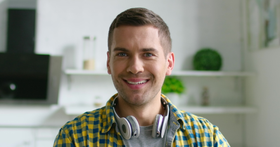 Portrait of young happy man putting wireless headset, smiling, looking at camera, full of positive emotions confidence, enjoying music, brunet, grey eyes, Caucasian, indoor. 4K, shot on RED camera. | Shutterstock HD Video #1034196578