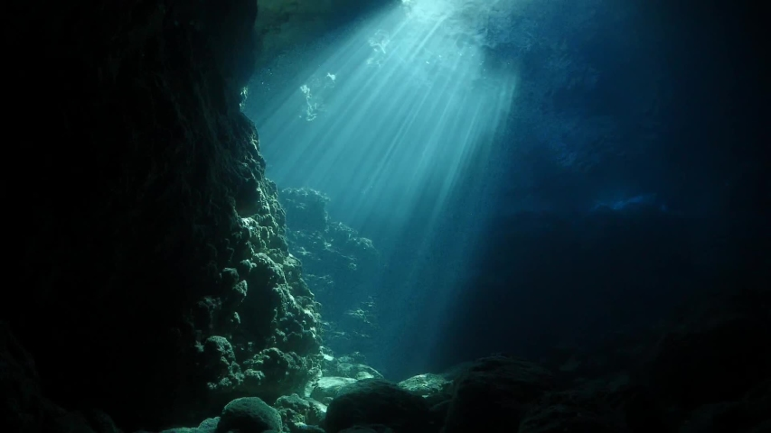 Sun rays sun beams and sun shine underwater in cave beautiful light scenery in ocean scuba divers to see | Shutterstock HD Video #1034204060