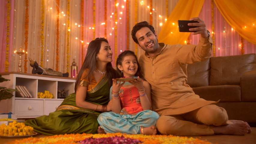 Diwali festival - Indian lovable family taking selfie or self photograph at home. Colorful decorate background. Asian/Indian young family taking photographs at an apartment with a plate of rose pet...
