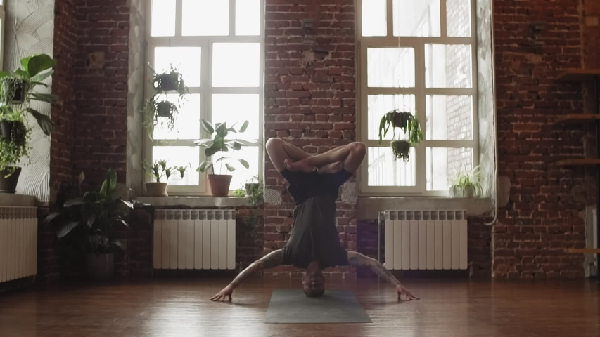 Hand standing pose. Young sporty man doing yoga in studio with wooden floor and big windows. Freedom, health and yoga concept with copy space.