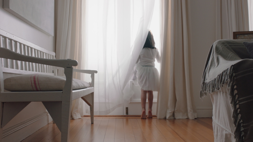 Happy little girl running through house wearing tutu opening curtains looking out window at beautiful new day with bright sunlight playful child feeling positive 4k footage